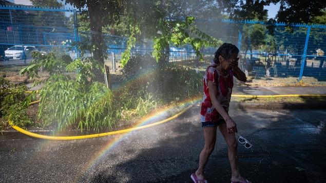 Une dame essuie son visage après s'être rafraîchie dans un jet d'eau.