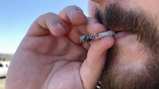 Photo d'un homme à barbe qui fume un joint.