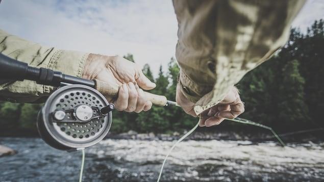Gros plan sur deux mains tenant une canne à pêche près d'une rivière.