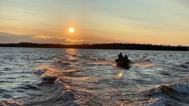 Un bateau sur un lac à l'aurore.