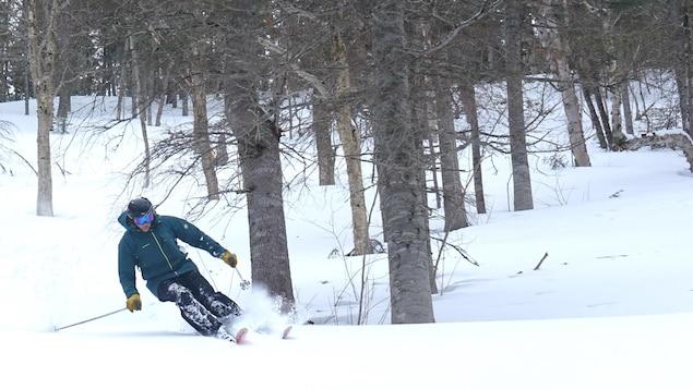 Un skieur fait une descente.