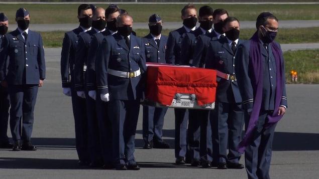 Plusieurs hommes masqués portent un cercueil.