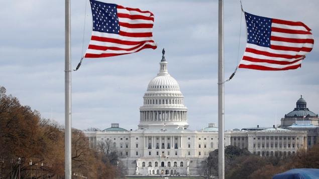 Vue panoramique du Capitole, derrière des drapeaux des États-Unis.