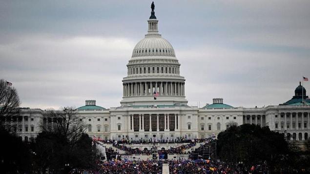 Vue d'ensemble de l'extérieur du Capitole, devant lequel des milliers de personnes sont réunies.