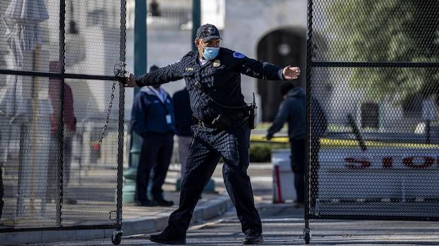 Un policier referme une haute clôture de sécurité au Capitole.