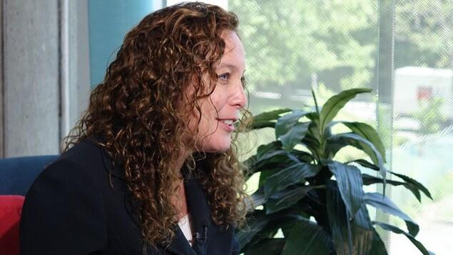 Une femme aux cheveux frisés est vue de profil et elle regarde droit devant elle. Elle a la bouche ouverte et semble esquisser un sourire.