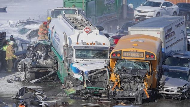 Un camion citerne et un autobus scolaire lourdement endommagés gisent sur la chaussée.