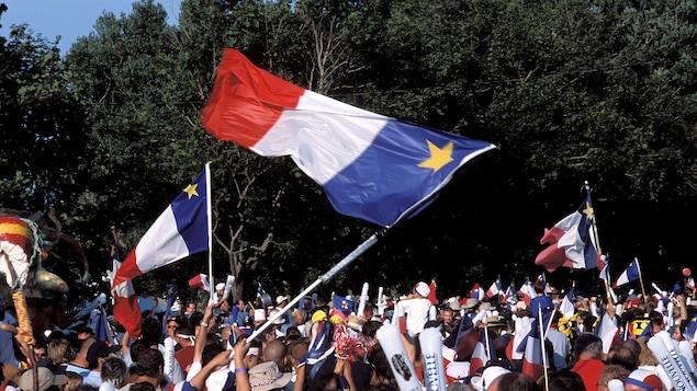 Une foule en liesse brandit des drapeaux acadiens