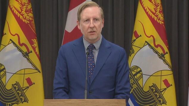 Dominic Cardy devant des drapeaux du Nouveau-Brunswick et du Canada s'adresse au public sur Internet.