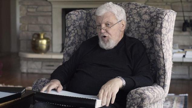 Le regretté Carl Grenier en entrevue dans sa résidence à l'été 2018. Sur ses genoux, le rapport confidentiel du Secrétariat temporaire pour l'examen des relations économiques après la souveraineté.