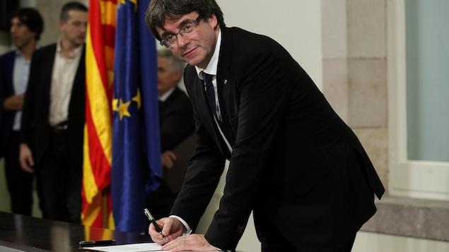 Le président Carles Puigdemont signant la déclaration d'indépendance de la Catalogne
