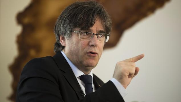 L'ex-président de la Catalogne, Carles Puigdemont, affiche un air sévère et a levé l'index qu'il pointe d'une façon accusatrice.