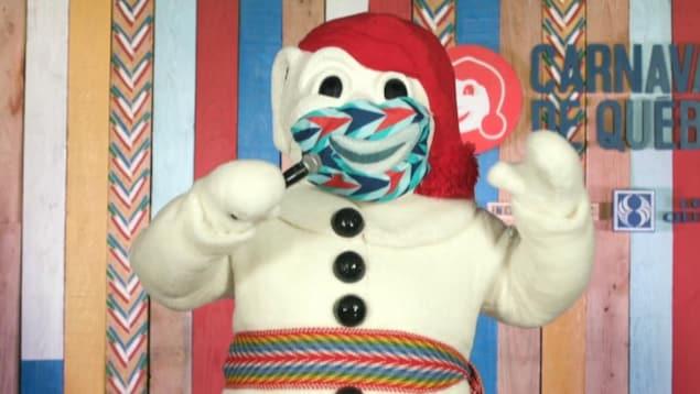 Le Bonhomme Carnaval sur une scène, il porte un masque et parle avec un micro