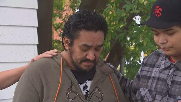 Un homme pleure, un adolescent à ses côtés pose sa main sur son épaule.