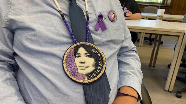 Un homme porte un pendentif fait en perles arborant le visage de Joyce Echaquan et la mention « Justice pour Joyce ».