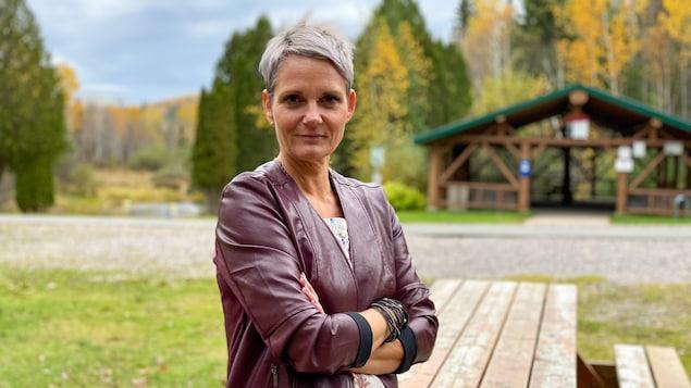Une femme aux cheveux courts gris croise les bras devant l'objectif.