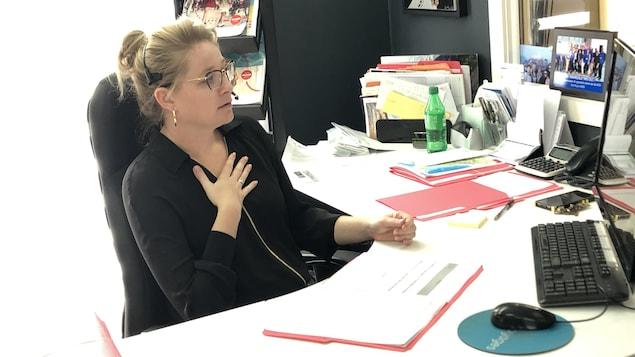 Une femme portant un micro casque parle au téléphone dans son bureau.