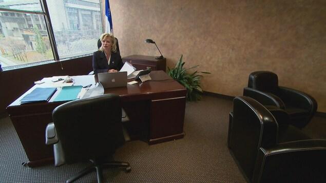 Caroline Proulx est assise à son bureau.