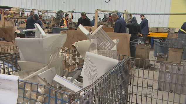 Des hommes travaillent dans un garage. Il y a beaucoup de matériel informatique.