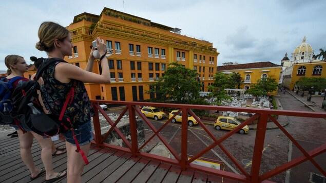 Trois femmes touristes prennent en photo des bâtiments et une église dans la vieille ville de Carthagène, en Colombie.