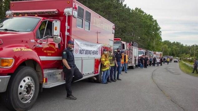 Plusieurs camions et pompiers le long de la route.