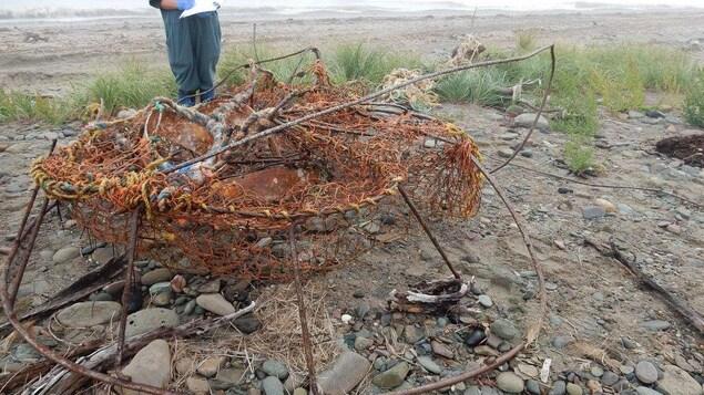 Un casier rouillé pour la pêche au crabe des neiges est examiné par un homme sur une plage.