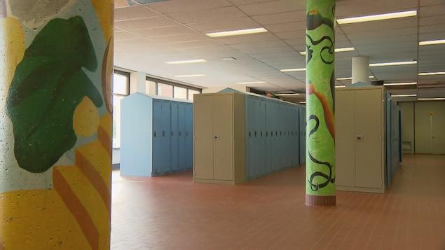 Trois rangée de casiers métalliques dans une école secondaire.