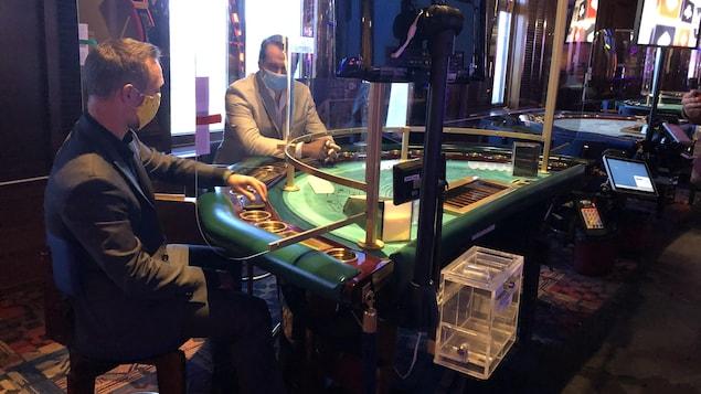 Deux hommes avec des masques installés à une table de jeux dans un casino.
