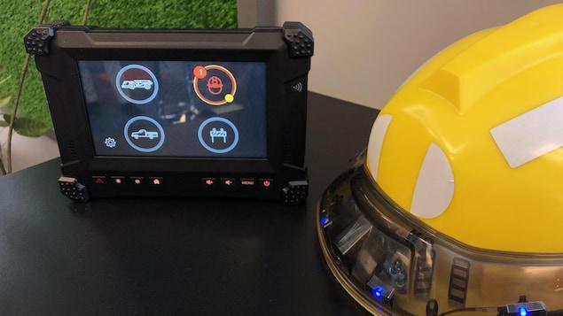 Une tablette électronique et un casque intelligent dont les lumières bleues sont allumées sont côte à côte sur une table.