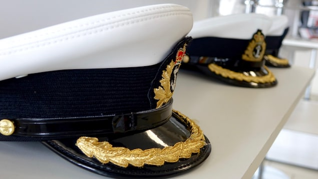 Une photo de trois casquettes d'officiers de la Marine royale canadienne