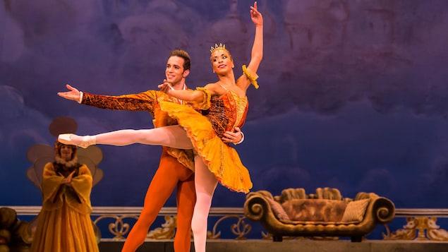 Un danseur et une danseuse faisant une arabesque sont sur scène.