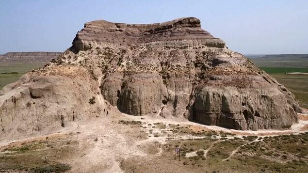 Une colline fait de sédiments rocheux au milieu d'un champ des Prairies canadiennes.