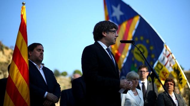 Il est au micro devant son vice-président, entourés tous les deux de drapeaux