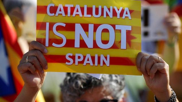 Une femme tient une affiche indiquant que la Catalogne n'est pas l'Espagne.