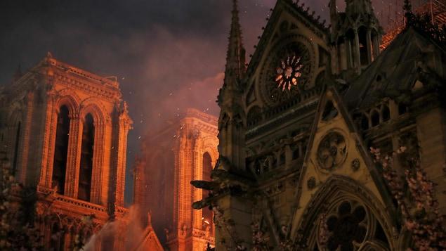Des étincelles remplissent l'air alors que des pompiers de Paris pulvérisent de l'eau pour éteindre les flammes lors de l'incendie de la cathédrale Notre-Dame de Paris.