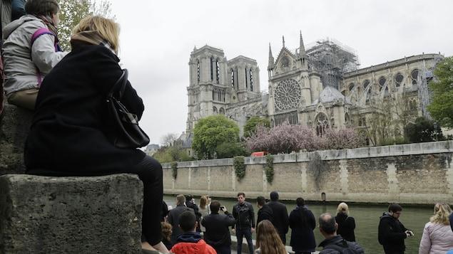 Une vingtaine de personnes sont sur un quai de la Seine, près de la cathédrale. Nombreux sont ceux qui prennent des photos.