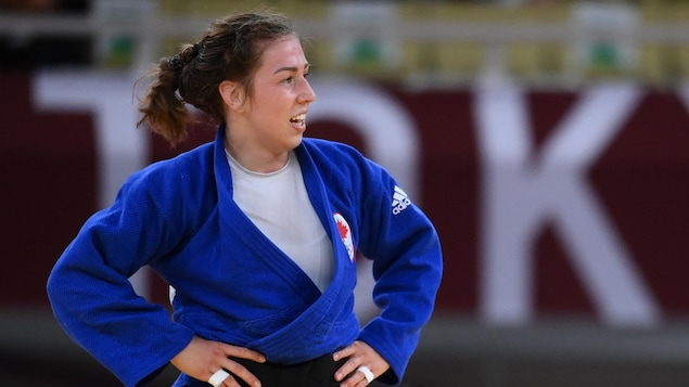 Les mains sur les hanches, Catherine Beauchemin-Pinard regarde à sa gauche sur le tatami.