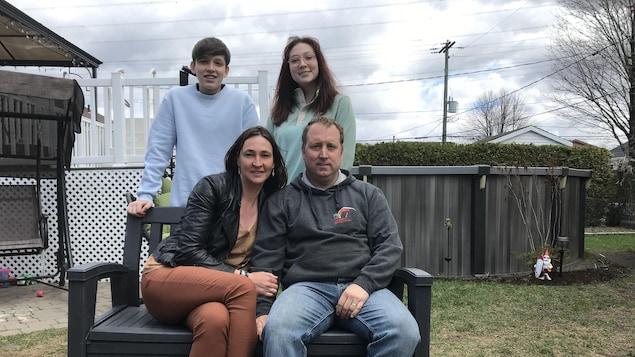 Catherine Bégin et Sunny Bouchard en compagnie de leurs enfants Léa-Gabrielle et Charles-Éric Bouchard, dans la cour de leur maison de Boischatel.