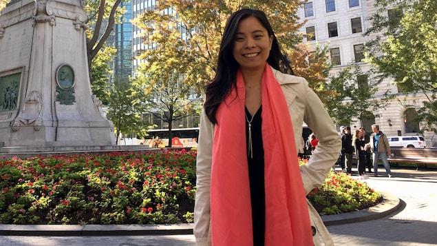 Cathy Wong debout près d'une statue dans un parc.