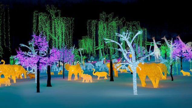 un paysage d'animaux et d'arbres illuminés et multicolores figés dans la neige