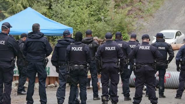 Una docena de policías frente a un campamento de protesta.