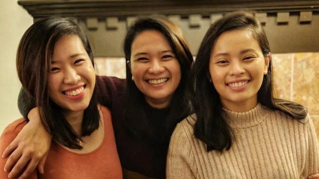 Anne Ignacio (au centre) pose avec ses deux soeurs devant un foyer.