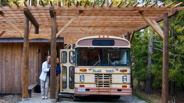 Un homme en sarrau et une femme se tiennent à côté d'un bus, sous une pergola de bois.