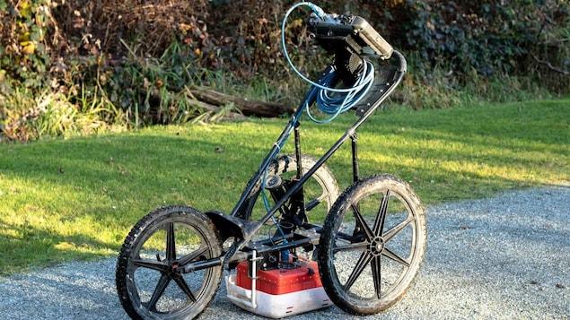 Un géoradar sur trois roues sur un sentier de gravier.