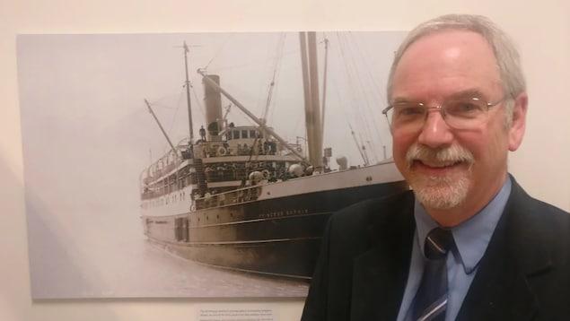 Un homme pose devant une ancienne photo d'un navire au charbon.