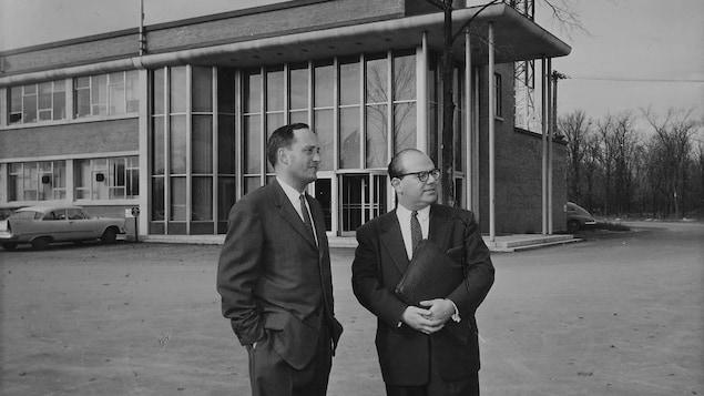 Georges Huard et Denis Townsend posant devant le bâtiment de la station de télévision.