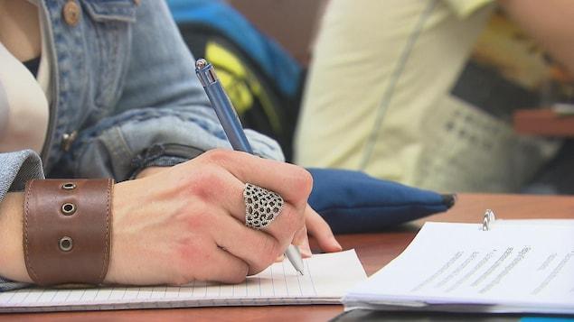 Une étudiante inscrit des notes sur une feuille.