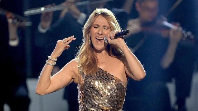 Céline Dion, qui porte une robe dorée, chante sur scène.