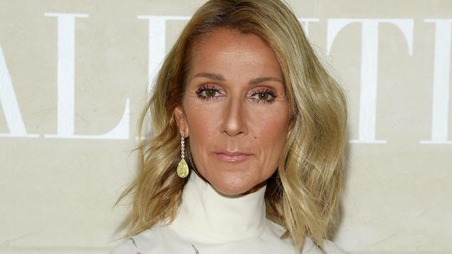 La femme blonde a une robe blanche et regarde la caméra.