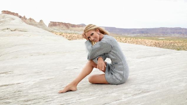 Céline Dion est assise sur un rocher dans un désert et elle sourit à la caméra.